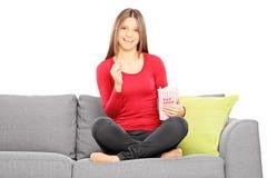 Giovane bella donna su un sofà che guarda TV e che mangia popcorn Fotografie Stock Libere da Diritti