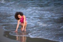 Giovane bella donna sulla linea della spuma alla spiaggia del mare Fotografia Stock