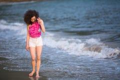 Giovane bella donna sulla linea della spuma alla spiaggia del mare Immagini Stock Libere da Diritti
