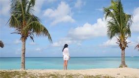 Giovane bella donna sulla spiaggia durante la vacanza tropicale archivi video