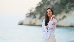 Giovane bella donna sulla spiaggia tropicale bianca stock footage