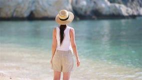 Giovane bella donna sulla spiaggia tropicale della sabbia bianca Ragazza caucasica nel fondo del cappello il mare archivi video