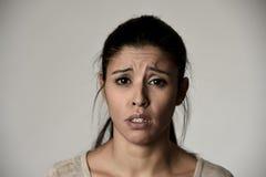 Giovane bella donna triste ispanica seria ed interessata nell'espressione facciale depressa preoccupata Fotografia Stock