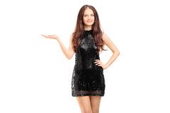 Giovane bella donna in un gesturing nero del vestito elegante Fotografie Stock