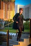 Giovane bella donna in un parco al tramonto su un fondo fotografia stock