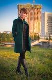 Giovane bella donna in un parco al tramonto su un fondo immagini stock