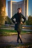 Giovane bella donna in un parco al tramonto su un fondo di hig fotografie stock