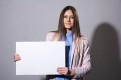 Giovane bella donna in un rivestimento con il foglio bianco Fotografia Stock