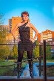 Giovane bella donna in un vestito nello stile militare nel parco di autunno immagini stock libere da diritti