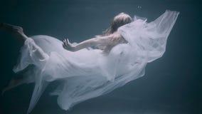 Giovane bella donna in vestito bianco che nuota underwater video d archivio