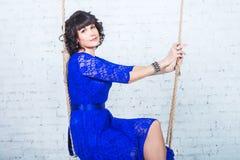 Giovane bella donna in vestito blu che si siede sul fondo dell'oscillazione del muro di mattoni bianco Fotografie Stock