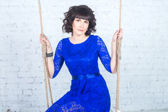 Giovane bella donna in vestito blu che si siede sul fondo dell'oscillazione del muro di mattoni bianco Immagini Stock Libere da Diritti