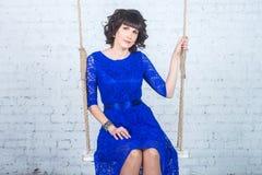 Giovane bella donna in vestito blu che si siede sul fondo dell'oscillazione del muro di mattoni bianco Immagine Stock Libera da Diritti