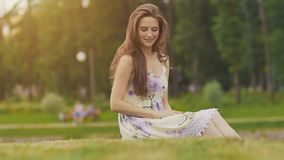 Giovane bella donna in vestito da estate con capelli lunghi che si siedono sull'erba in parco verde e che parlano sul telefono, s archivi video