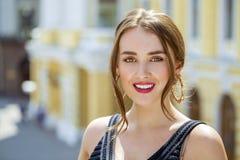 Giovane bella donna in vestito nero che ci posa all'aperto in soleggiato Fotografia Stock Libera da Diritti