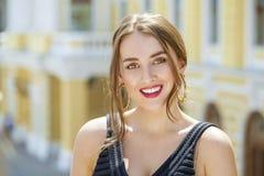Giovane bella donna in vestito nero che ci posa all'aperto in soleggiato Fotografie Stock Libere da Diritti