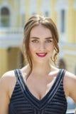 Giovane bella donna in vestito nero che ci posa all'aperto in soleggiato Fotografia Stock