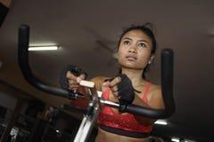 Giovane bella e donna attiva asiatica sudata che prepara duro riciclaggio e guida sull'allenamento statico della bici alla palest Immagini Stock Libere da Diritti