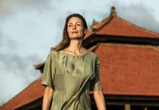 Giovane bella e donna bionda attraente che posa come modello di moda di bellezza isolato davanti al tempio asiatico che indossa D immagine stock libera da diritti