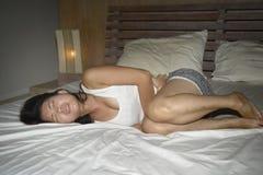 Giovane bella e donna cinese abbastanza asiatica che si trova sul sentiresi male del letto e crampo di sofferenza indisposto di s immagini stock libere da diritti