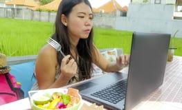 Giovane bella e donna cinese asiatica felice che lavora all'aperto con il caffè del fondo dell'erba verde della rete del computer Immagine Stock