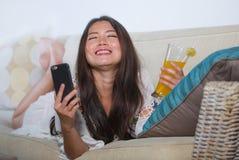 Giovane bella e donna cinese asiatica felice sul suo 20s o 30s che si trova allo strato del sofà del salone che beve usin sano de Fotografie Stock Libere da Diritti