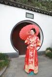 Giovane, bella e donna cinese elegante che porta il vestito rosso di seta di una sposa cinese tipica, ornato con Phoenix e il dra immagini stock libere da diritti
