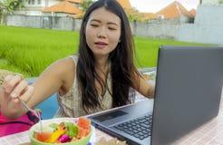 Giovane bella e donna coreana asiatica felice che lavora all'aperto con il caffè del fondo dell'erba verde della rete del compute Immagine Stock