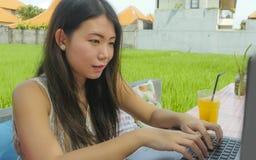 Giovane bella e donna coreana asiatica felice che lavora all'aperto con il caffè del fondo dell'erba verde della rete del compute Immagini Stock Libere da Diritti