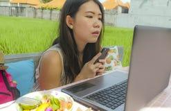 Giovane bella e donna coreana asiatica felice che lavora all'aperto con il caffè del fondo dell'erba verde della rete del compute Fotografia Stock