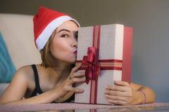 Giovane bella e donna felice in contenitore di tenuta e baciante di cappello di Santa del regalo di Natale con sorridere rosso de fotografie stock