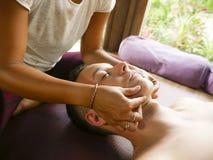 Giovane bella e donna tailandese asiatica esotica del terapista che d? testa tradizionale e massaggio facciale di balinese all'uo immagine stock libera da diritti