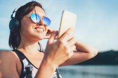 Giovane bella femmina che pareggia e che ascolta la musica facendo uso dello smartphone e delle cuffie senza fili allegramente ch immagine stock