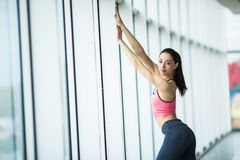 Giovane bella giovane donna in abiti sportivi che fanno allungamento mentre stando davanti alla finestra alla palestra Immagini Stock