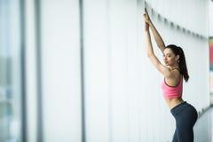 Giovane bella giovane donna in abiti sportivi che stanno davanti alla finestra alla palestra Fotografia Stock