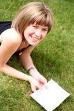 Giovane bella lettura della ragazza nella sosta Fotografie Stock Libere da Diritti