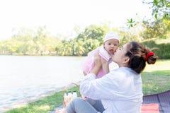 Giovane bella madre asiatica che bacia il suo piccolo bambino 4 mesi di ragazza Famiglia; madre e figlia che hanno un tempo liber fotografia stock libera da diritti