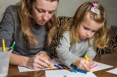 Giovane bella madre con il suo tiraggio della figlia con le matite variopinte su carta, famiglia felice fotografia stock libera da diritti