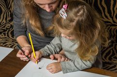 Giovane bella madre con il suo tiraggio della figlia con le matite variopinte su carta, famiglia felice immagine stock