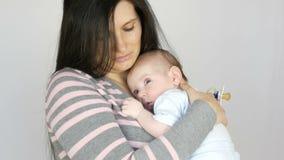 Giovane bella madre dai capelli lunghi mora con il neonato di due mesi che dorme nelle sue armi La mamma la culla archivi video