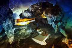 Giovane bella meditazione della donna vicino alla statua di Buddha del gigante dentro in caverna enorme fotografie stock