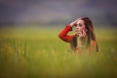Giovane bella posa castana vietnamita in un vestito rosso Immagini Stock Libere da Diritti