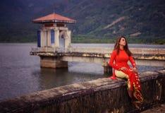 Giovane bella posa castana vietnamita in un vestito rosso Fotografia Stock