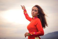 Giovane bella posa castana vietnamita in un vestito rosso Immagine Stock Libera da Diritti