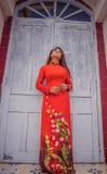 Giovane bella posa castana vietnamita in un vestito rosso Immagini Stock