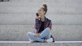 Giovane bella ragazza afroamericana che parla sullo Smart Phone, all'aperto
