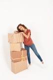 Giovane bella ragazza allegra che sta accanto alla pila di grandi contenitori di regalo isolati Fotografia Stock Libera da Diritti