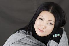 Giovane bella ragazza asiatica su un fondo scuro Fotografia Stock Libera da Diritti