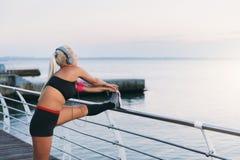 Giovane bella ragazza atletica con capelli biondi lunghi in cuffie che ascolta la musica e che fa allungamento all'alba sopra il  Fotografia Stock