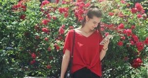 Giovane bella ragazza attraente astuta in esultanza rossa della blusa del messaggio in suo smartphone, cespuglio con le rose urba video d archivio